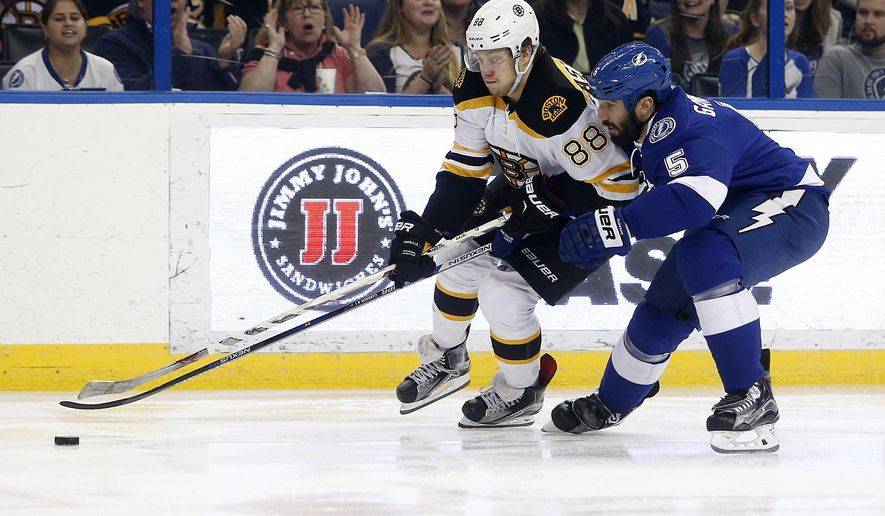 Boston Bruins left wing David Pastrnak (88), of the Czech Republic, battles for the puck against Tampa Bay Lightning defenseman Jason Garrison (5) during the first period of an NHL hockey game, Tuesday, March 8, 2016, in Tampa, Fla. (AP Photo/Brian Blanco)