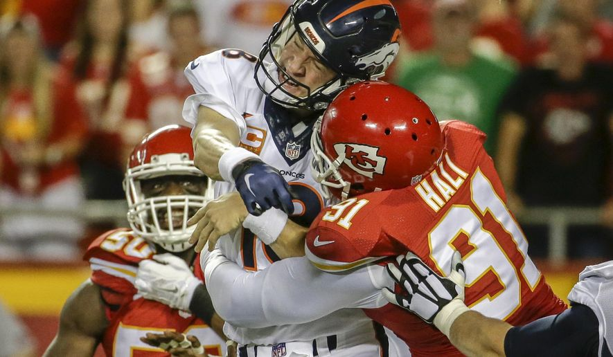 FILE - In this Sept. 17, 2015, file photo, Kansas City Chiefs linebacker Tamba Hali (91) makes contact with Denver Broncos quarterback Peyton Manning (18) after the throw, in the first half of an NFL football game in Kansas City, Mo. A person familiar with the situation told The Associated Press that the Chiefs and Tamba Hali have agreed to a three-year contract to keep the veteran linebacker in Kansas City. The person spoke on the condition of anonymity Tuesday, March 8, 2016,  because the deal had not been announced. (AP Photo/Charlie Riedel)