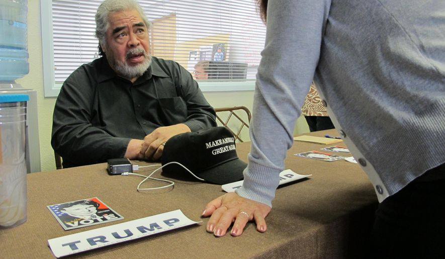 Nathan Paikai, a minister who's leading Trump's campaign efforts in Hawaii, talks to a voter on Monday, March 7, 2016, in Honolulu. The Hawaii Republican Party is holding its Republican presidential caucus on Tuesday. (AP Photo/Cathy Bussewitz)