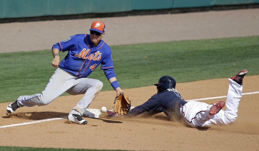 Atlanta Braves' Erick Aybar, right, slides into third base as New York Mets shortstop Wilmer Flores waits for the ball to make the tag during the fifth inning of a spring training baseball game, Tuesday, March 8, 2016, in Kissimmee, Fla. (AP Photo/John Raoux)