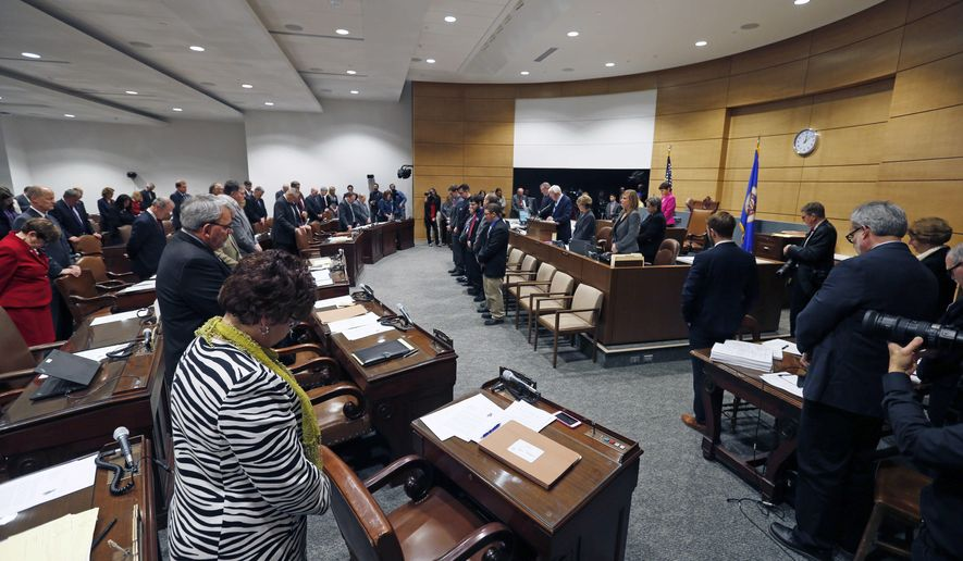 State Senators bow during the opening prayer at the temporary Senate chamber in the new State Senate building as the 2016 legislative session got underway Tuesday, March 8, 2016, in St. Paul, Minn. The Senate chamber in the State Capitol is undergoing restoration along with the entire Capitol. (AP Photo/Jim Mone)