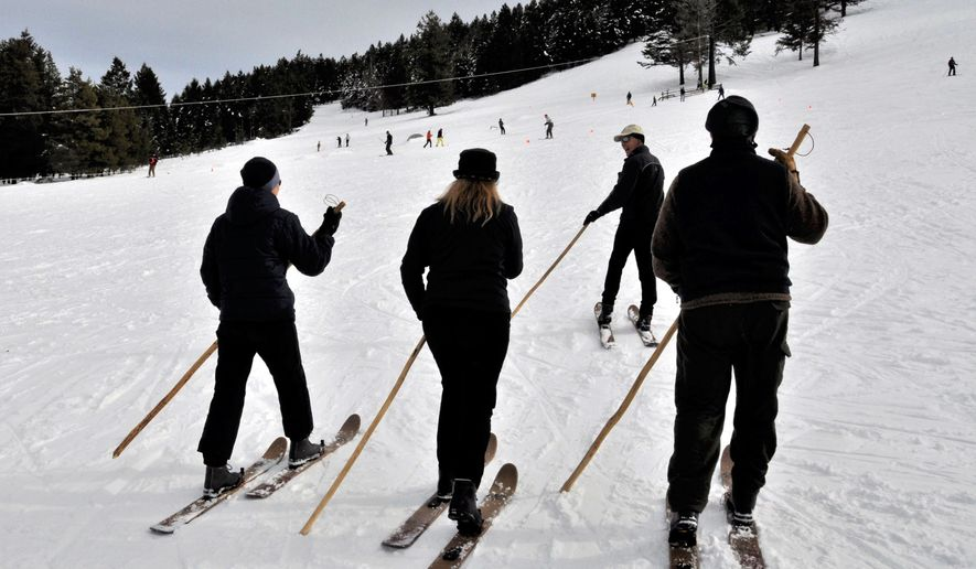 Don Portman leads a group of skiers trying out Altai Hok skis at Sitzmark Ski Area. Instead of ski poles, they each hold a single tiak used for centuries by herdsmen in the Altai Mountains of northern Asia. (Rich Landers/The Spokesman-Review via AP)