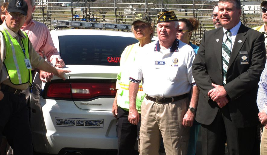 """Saluda County Sheriff John Perry, right, poses after a ceremony where he announced he is putting """"In God We Trust"""" stickers on all of his patrol cars on Monday, March 7, 2016 in Saluda, S.C. Perry says the stickers are not an election year stunt, even though he faces two Republican challengers, including the last elected sheriff who quit and pleaded guilty to improperly using inmate labor at his home. (AP Photo/Jeffrey Collins)"""