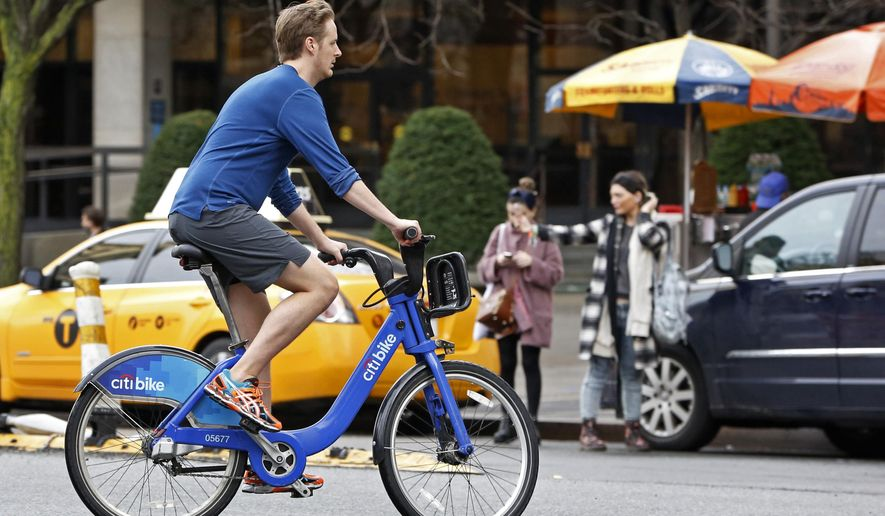 FILE - In this Dec. 24, 2015 file photo, a man wearing shorts, sneakers and no socks rides a rental bike through a downtown Manhattan street on Christmas Eve. Federal meteorologists say the winter that has just ended was the hottest in U.S. records, thanks to the combination of El Nino and man-made global warming. (AP Photo/Kathy Willens, File)
