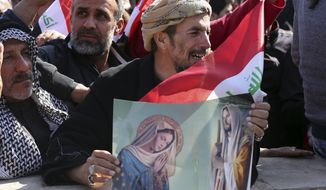 An Iraqi man weeps as he holds a Christian religious poster depicting Jesus and the Virgin Mary during a demonstration calling for governmental reform in Tahrir Square in Baghdad on Feb. 26. (Associated Press)
