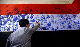A boy gets his hand print on a Yemeni flag during a gathering by held Shiite rebels, known as Houthis, against Saudi-led airstrikes in Sanaa, Yemen, Wednesday, March 9, 2016. (AP Photo/Hani Mohammed)