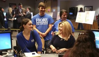 Supporters join Republican Assemblywoman Michele Fiore, right, as she files paperwork in Las Vegas Wednesday, March 9, 2016, to run in Nevada's 3rd Congressional District. Fiore is an outspoken, two-term state lawmaker best known for her love of guns, support for Nevada rancher Cliven Bundy and her recent intervention to coax the last remaining occupier from a federal wildlife refuge in Oregon. (AP Photo/Michelle Rindels)