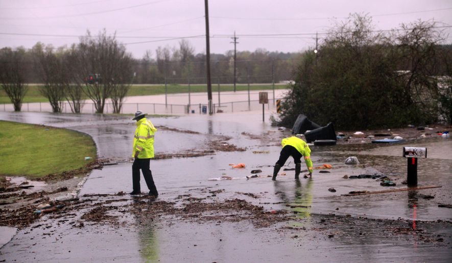 Louisiana State police help clear the road of debris at the entrance in the Tall Timbers subdivision in Haughton, La. Wednesday March 9, 2016. Severe thunderstorms have caused major flooding and closed all schools in the area. Several parishes in northwest Louisiana have declared a state of emergency over widespread flooding, and the National Guard is being sent in to help.  (AP Photo/Mike Silva)