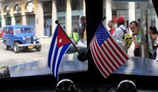 FILE - In this March 22, 2013 file photo, miniature flags representing Cuba and the U.S. are displayed on the dash of a classic American car in Havana, Cuba. After decades of U.S. efforts to foment democracy by backing Cuba's dissidents and their demands for swift political change, President Barack Obama's trip in March 2016 will showcase a 180-degree turn in U.S. policy toward the island. The U.S. is wagering that re-forging links between the U.S. and Cuba will do more to change Cuba's single-party government and centrally planned economy than a half-century of confrontation. (AP Photo/Franklin Reyes, File)