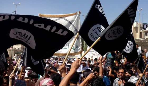 Demonstrators chant pro-Islamic State slogans as they wave the group's flags in front of the provincial government headquarters in Mosul, Iraq, on June 16, 2014. (Associated Press) **FILE**