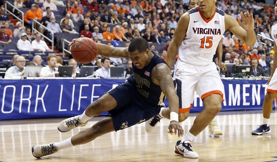 Georgia Tech guard Marcus Georges-Hunt (3) falls to the floor in front of Virginia guard Malcolm Brogdon (15) during the first half of an NCAA college basketball game in the Atlantic Coast Conference men's tournament, Thursday, March 10, 2016, in Washington. (AP Photo/Alex Brandon)