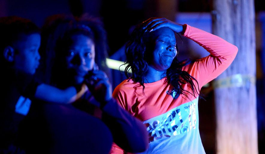 A woman reacts at the scene of a deadly shooting in Wilkinsburg, Pa., Thursday, March 10, 2016. Police say multiple people were killed in the shooting late Wednesday and several were injured in suburban Pittsburgh. (Michael Henninger/Pittsburgh Post-Gazette via AP)