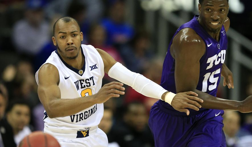 West Virginia guard Jevon Carter (2) and TCU forward JD Miller (15) chase a loose ball during the first half of an NCAA college basketball game in the quarterfinals of the Big 12 conference tournament in Kansas City, Mo., Thursday, March 10, 2016. (AP Photo/Orlin Wagner)