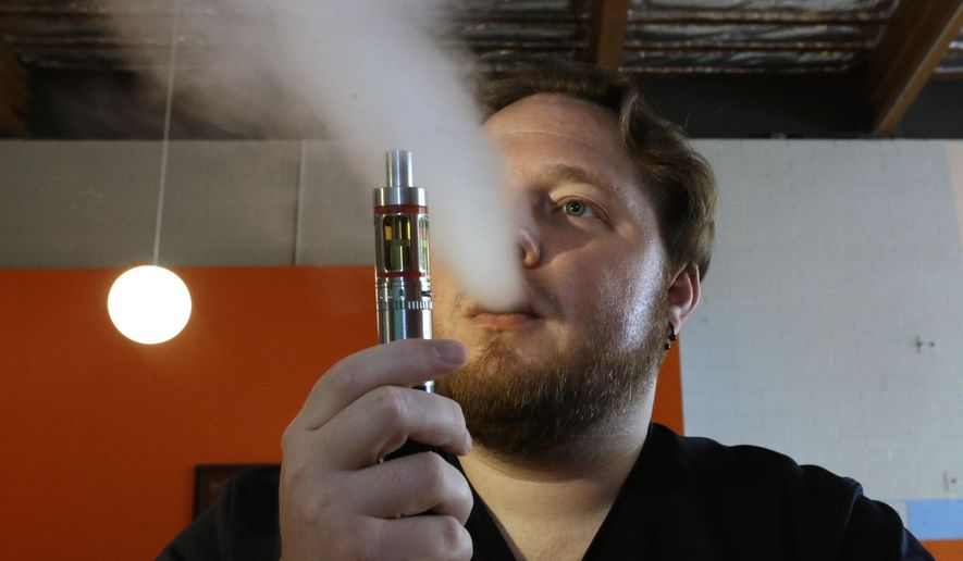 FILE -- In this July 16, 2015 file photo, Bruce Schillin, 32, exhales vapor from an e-cigarette at the Vapor Spot, in Sacramento, Calif. California's Senate is poised to vote Thursday, March 10, 2016, on a package of anti-smoking measures that include raising the smoking age to 21 and to regulate electronic cigarettes as tobacco, setting restrictions on their use. (AP Photo/Rich Pedroncelli, File)