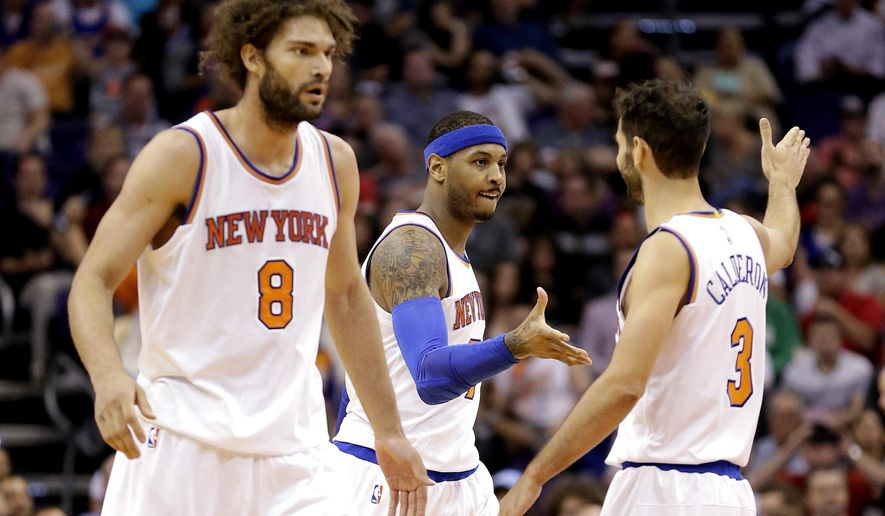 New York Knicks' Carmelo Anthony, center, is congratulated by teammate Jose Calderon (3) as Robin Lopez walks to the bench against the Phoenix Suns during the first half of an NBA basketball game Wednesday, March 9, 2016, in Phoenix. (AP Photo/Matt York)