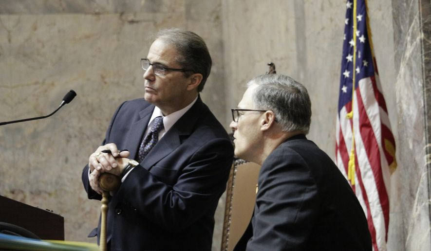 Gov. Jay Inslee, right, talks with Lt. Gov. Brad Owen in the Senate chamber on the last day of the regularly scheduled 60-day legislative session, Thursday, March 10, 2016, in Olympia, Wash. Lawmakers face a special session after not finishing a supplemental budget on time.  (AP Photo/Rachel La Corte)