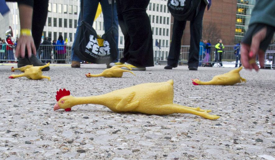 Volunteers pick up rubber chickens as part of Gilda's LaughFest at Calder Plaza in downtown Grand Rapids, Mich., Thursday, March 10, 2016. Hundreds of people threw a rubber chicken Thursday outside city hall in Grand Rapids, but organizers didn't get enough to set a record. (Cory Morse/The Grand Rapids Press via AP) MANDATORY CREDIT