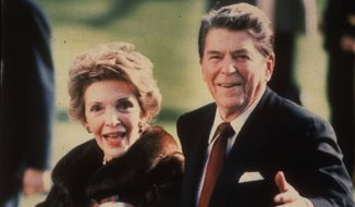 "This December 1986 file photo shows first lady Nancy Reagan holding the Reagans' pet Rex, a King Charles spaniel, as she and President Reagan walk on the White House South lawn. The former first lady will be buried beside her ""Ronnie"" Friday, March 11, 2016, at the library they loved, after being mourned and celebrated by family and hundreds of friends from Hollywood, Washington and beyond in a private service. Mrs. Reagan, who died Sunday at 94, planned the smallest details of her funeral. (AP Photo/Dennis Cook, File)"