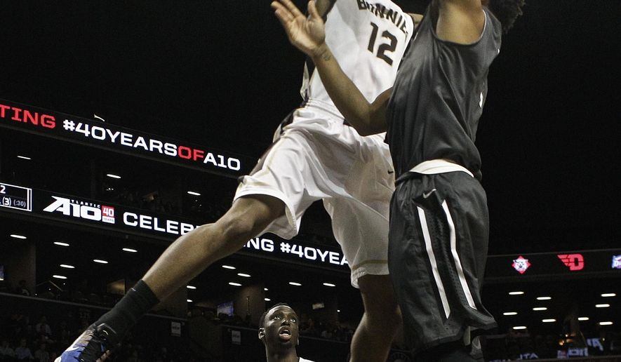 St. Bonaventure's Denzel Gregg (12) blocks a shot by Davidson's Jordan Barham as teammate Nelson Kaputo (4) watches during the first half of an NCAA college basketball game during the Atlantic 10 men's tournament Friday, March 11, 2016, in New York. (AP Photo/Frank Franklin II)