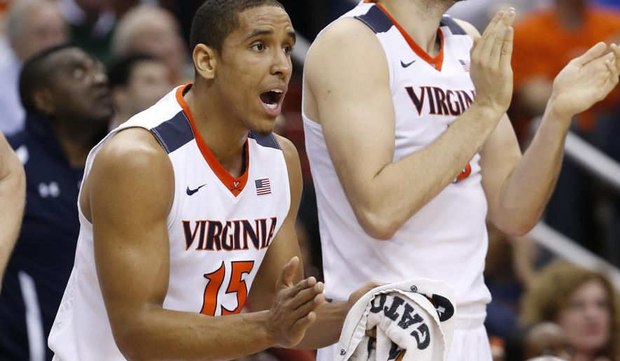 Virginia guard Malcolm Brogdon (15) and center Mike Tobey cheer their team during the first half of an NCAA college basketball game against Miami in the Atlantic Coast Conference men's tournament, Friday, March 11, 2016, in Washington. (AP Photo/Steve Helber)