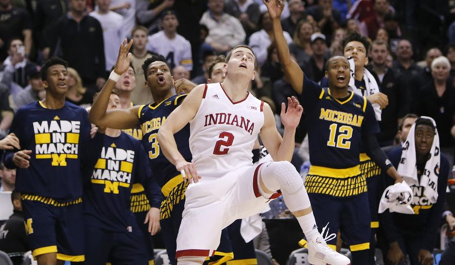 Michigan's Kameron Chatman (3) watches his game winning three point basket against Indiana's Nick Zeisloft (2) in the second half of an NCAA college basketball game in the quarterfinals at the Big Ten Conference tournament, Friday, March 11, 2016, in Indianapolis. Michigan won 72-69. (AP Photo/Kiichiro Sato)