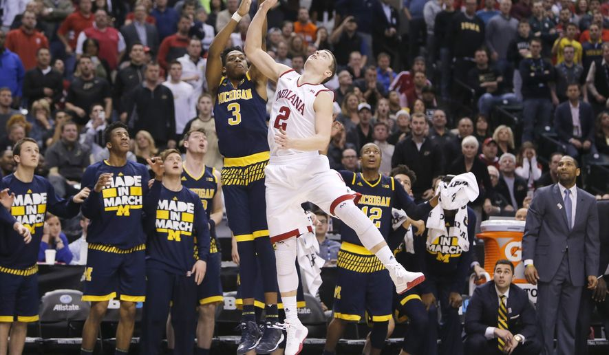 Michigan's Kameron Chatman (3) scores a game winning three point basket against Indiana's Nick Zeisloft (2) in the second half of an NCAA college basketball game in the quarterfinals at the Big Ten Conference tournament, Friday, March 11, 2016, in Indianapolis. Michigan won 72-69. (AP Photo/Kiichiro Sato)