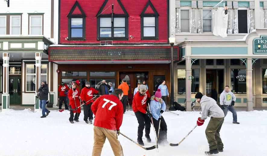 Two casually formed but fiercely rivalrous street hockey teams -- the Mackinac Island Red Wings and the St. Ignace Storm -- compete in the fifth of a nine-week street hockey tournament on Lake Shore Drive in downtown Mackinac Island on Wednesday, Feb. 17, 2016. The Bynoe Street Hockey League was formed about 10 years ago by Jamie Bynoe, one of about 500 members of Mackinac Island's close-knit community of year-round residents. The nine-game series is played Wednesdays at 4:30 on the downtown streets, ending in a St. Patrick's Day final for the Bynoe Championship Cup.  (Emily Rose Bennett/The Grand Rapids Press via AP)  (Emily Rose Bennett | MLive.com)