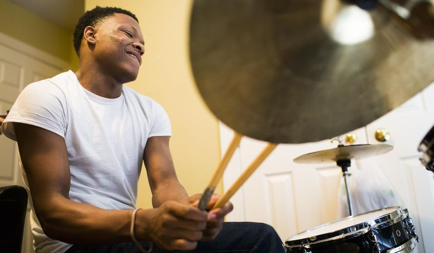 ADVANCE FOR WEEKEND EDITIONS - In this Friday, March 4, 2016 photo, Isaiah Kingston, 17, practices the drums in his bedroom with his music teacher John Battle of John Battle Arts in Rocky Mount, N.C. Kingston started playing the drums again while recovering from serious head and leg injuries from being robbed and beaten on July, 1, 2015, in Baltimore, MD. (Abbi O'Leary/The Rocky Mount Telegram via AP) MANDATORY CREDIT