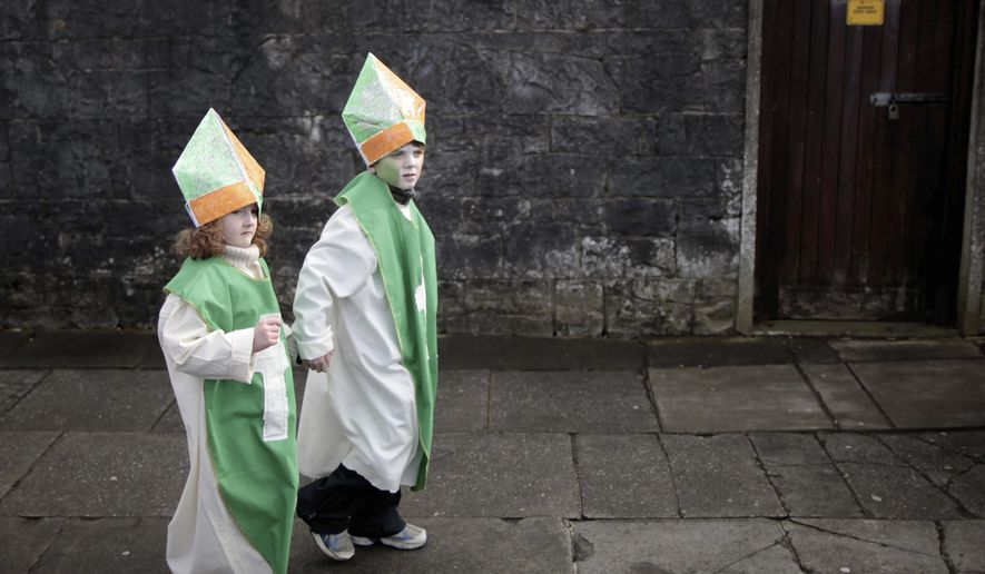 FILE - In this March 17, 2013 file photo, children make their way to the St Patrick's Day parade during the celebrations in Limerick, Ireland. Just in time for St. Patrick's Day, March 17, 2016, genealogical research website Ancestry.com is making available 10 million Catholic parish records from Ireland available online for free to help people trace their Irish heritage. The documents, in English and Latin, date from 1655 to 1915. (AP Photo/Peter Morrison, File)