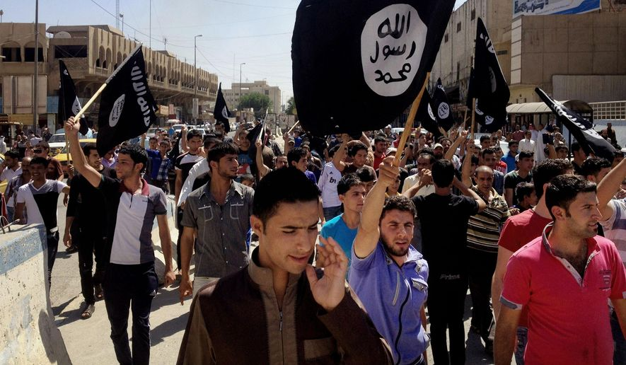 In this Monday, June 16, 2014, file photo, demonstrators chant pro-al-Qaeda-inspired Islamic State of Iraq and the Levant (ISIL) as they carry al Qaeda flags in front of the provincial government headquarters in Mosul, 225 miles (360 kilometers) northwest of Baghdad, Iraq. (AP Photo, File)