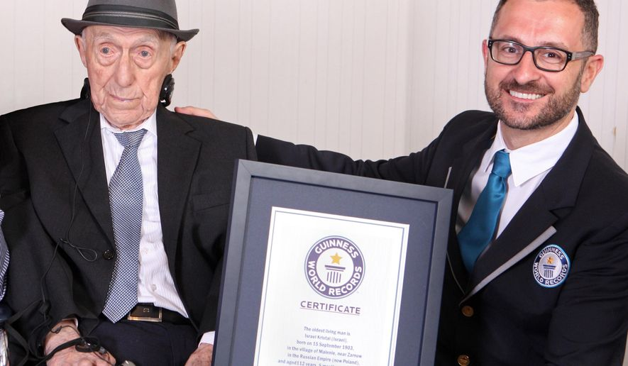 In this photo supplied by Guinness World Records, Marco Frigatti, Head of Records for Guinness World Records, right, presents Israel Kristal a certificate for being the oldest living man, in Haifa, Israel, Friday, March 11, 2016.  Guinness said in a statement that Kristal is 112 years and 178 days old as of March 11. Guinness said Kristal was born in 1903 to an Orthodox Jewish family near the town of Zarnow in Poland. However, Susannah Mushatt Jones, an American who is 115, is both the oldest living person and the oldest living woman. (Dvir Rosen/Guinness World Records via AP)