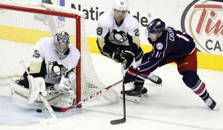 Pittsburgh Penguins goalie Marc-Andre Fleury, left, and teammate Ian Cole, center, work to stop a shot by Columbus Blue Jackets' Matt Calvert during the third period of an NHL hockey game in Columbus, Ohio Friday, March 11, 2016. Pittsburgh won 3-2. (AP Photo/Paul Vernon)