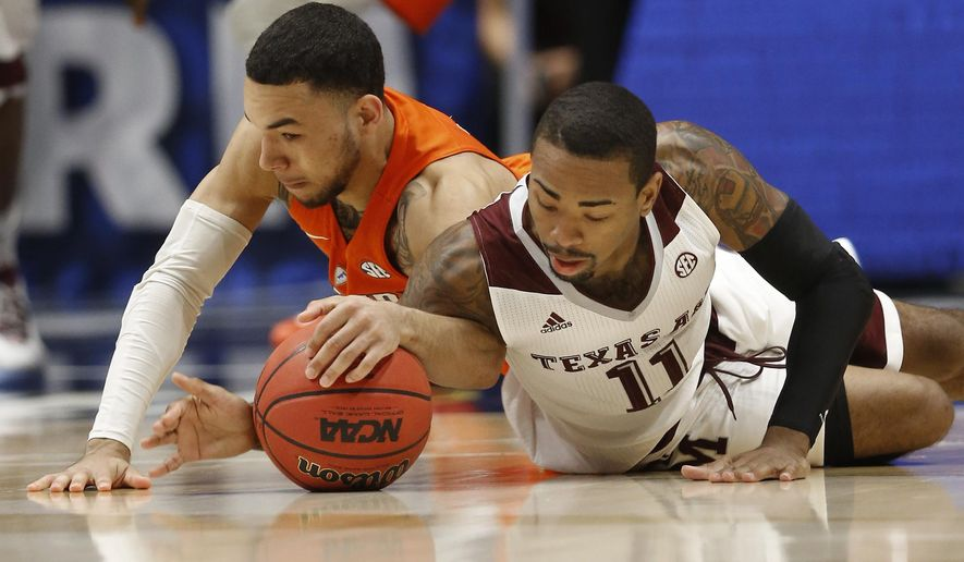 Florida's Chris Chiozza, left, and Texas A&M's Anthony Collins, right, battle for a loose ball during the first half of an NCAA college basketball game in the Southeastern Conference tournament in Nashville, Tenn., Friday, March 11, 2016. (AP Photo/John Bazemore)