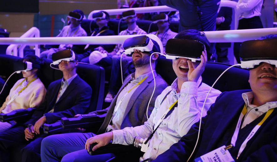FILE - In this Jan. 6, 2016 file photo, people react as they wear Samsung Gear VR goggles at CES International in Las Vegas. VR is a habitat of countless possibilities, an exhilarating refuge that yanks one from the sidelines and thrusts them into the action. (AP Photo/John Locher, File)