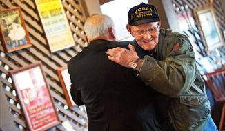 Max Garland, a Korean War veteran and the group organizer, greets Paul Galanti, a Vietnam prisoner of war, March 8, 2016 at the Veterans Breakfast Club of Fredericksburg meeting at Craker Barrell of Central Park in Fredericksburg, Va. (Dave Ellis/The Free Lance-Star via AP)