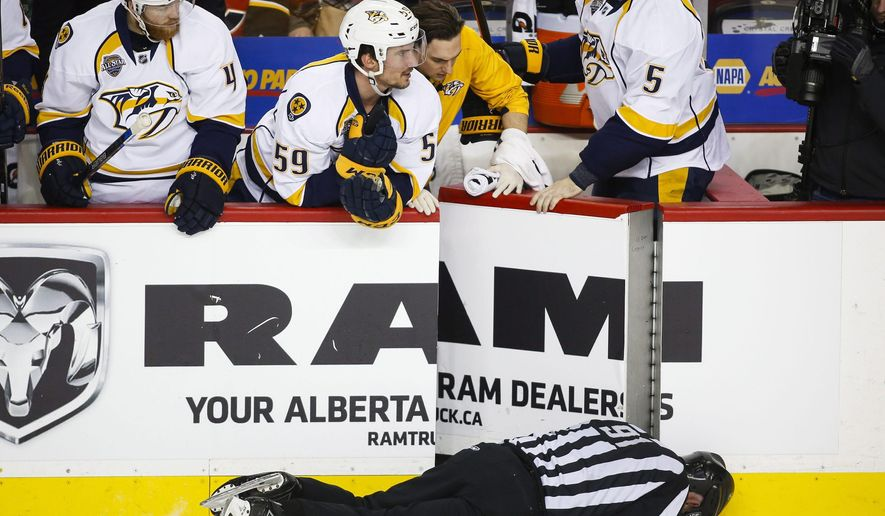 FILE - This Jan. 27, 2016 file photo shows Nashville Predators' players looking over the bench at linesman Don Henderson after he was hit by Calgary Flames' Dennis Wideman during second period NHL hockey action in Calgary, Alberta. Wideman's 20-game suspension for physically abusing the official has been reduced to 10 games by an independent arbitrator, Friday, March 11, 2016. (Jeff McIntosh/The Canadian Press via AP)