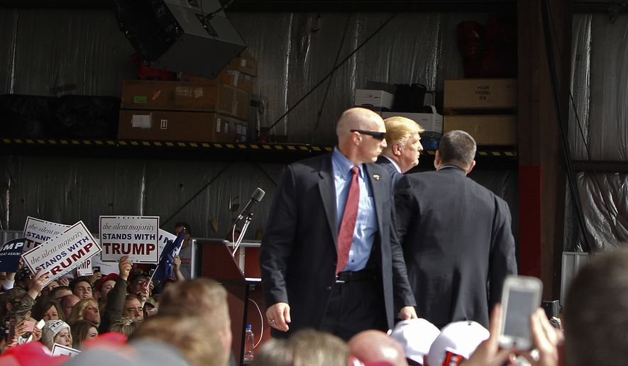 Secret Service agents guard Republican presidential candidate, businessman Donald Trump, on the stage after a man tried to breach the security buffer at his campaign event at the Wright Brothers Aero Hangar Saturday, March 12, 2016, in Vandalia, Ohio. (AP Photo/Kiichiro Sato)