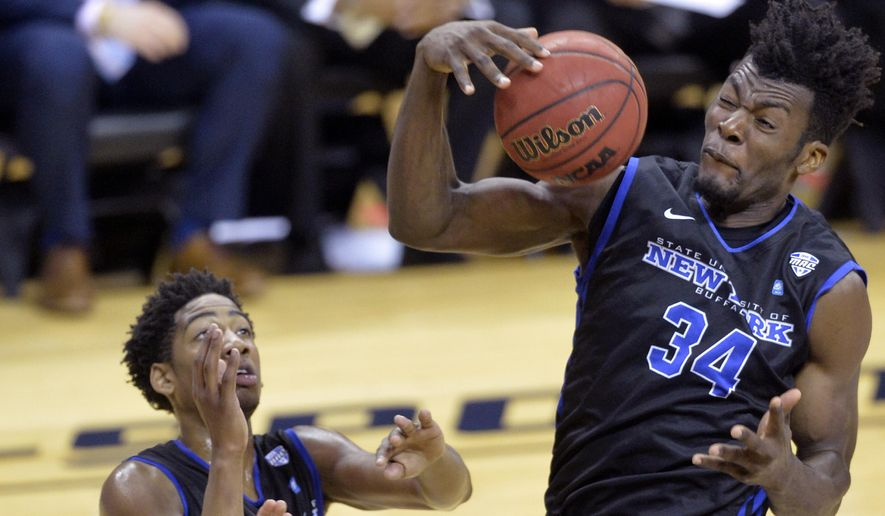 Buffalo's forward Ikenna Smart, right, rebounds beside CJ Massinburg in the first half of an NCAA college basketball game against Akron in the championship of the Mid-American Conference men's tournament, Saturday, March 12, 2016, in Cleveland. (AP Photo/David Richard)