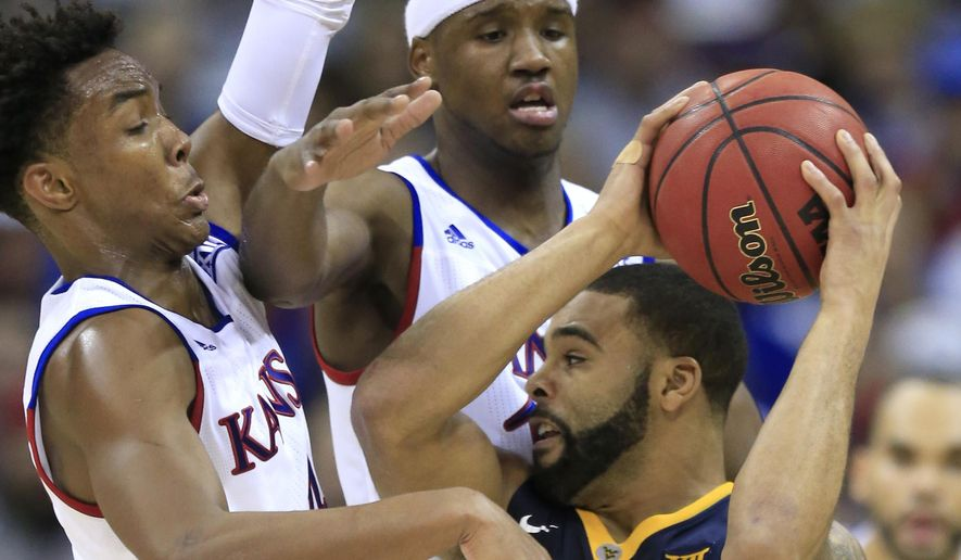 West Virginia guard Jaysean Paige (5) looks for help while covered by Kansas guard Devonte' Graham, left, and forward Carlton Bragg Jr., center, during the first half of an NCAA college basketball game in the finals of the Big 12 conference tournament in Kansas City, Mo., Saturday, March 12, 2016. (AP Photo/Orlin Wagner)