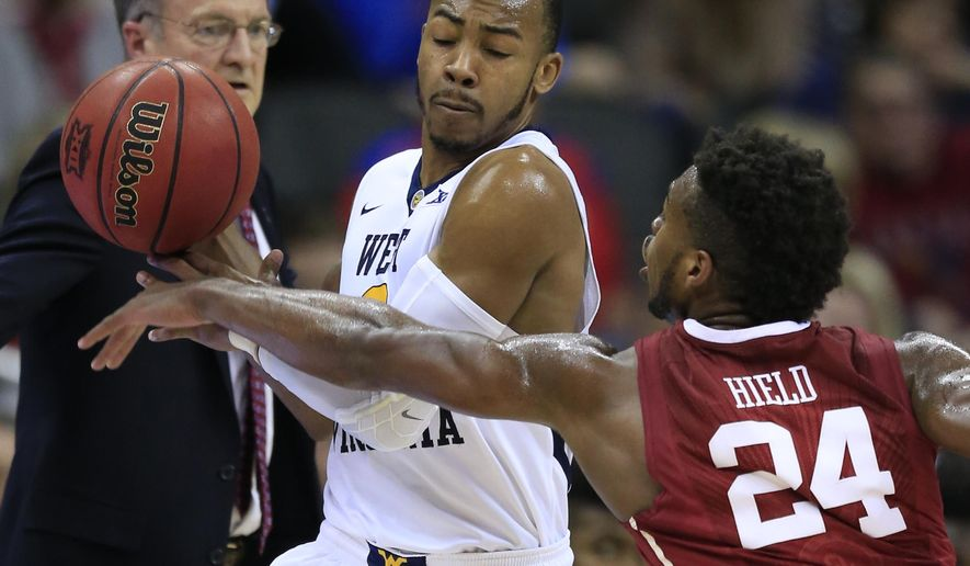 Oklahoma guard Buddy Hield (24) knocks the ball away from West Virginia guard Jevon Carter (2) during the first half of an NCAA college basketball game in the semifinals of the Big 12 conference tournament in Kansas City, Mo., Friday, March 11, 2016. (AP Photo/Orlin Wagner)