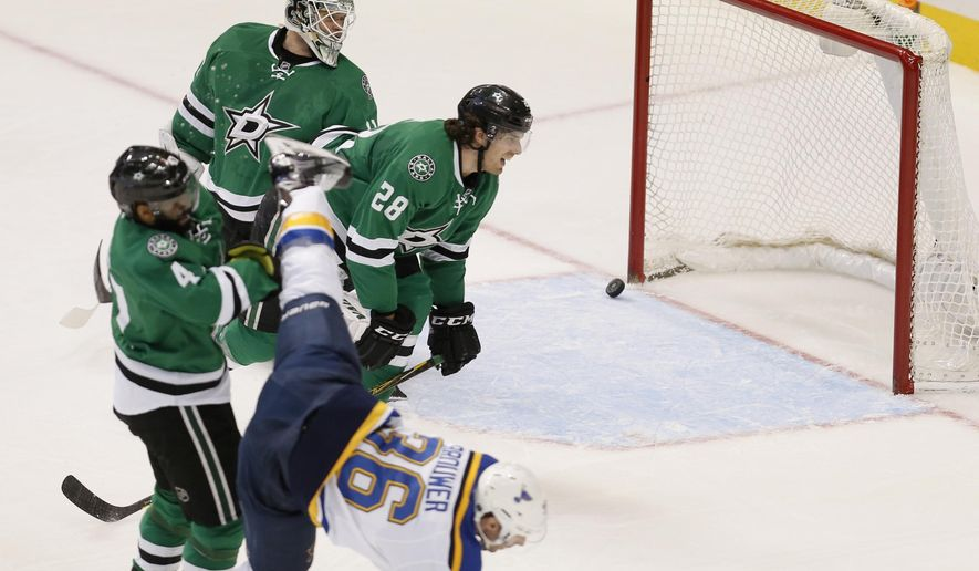 CORRECTS TO SATURDAY NOT MONDAY - St. Louis Blues forward Troy Brouwer (36) scores a goal while being checked off of his skates by Dallas Stars defenseman Jason Demers (4) as defenseman Stephen Johns (28) and goalie Antti Niemi (31) look on during the first period of an NHL hockey game Saturday, March 12, 2016, in Dallas. (AP Photo/Brandon Wade)