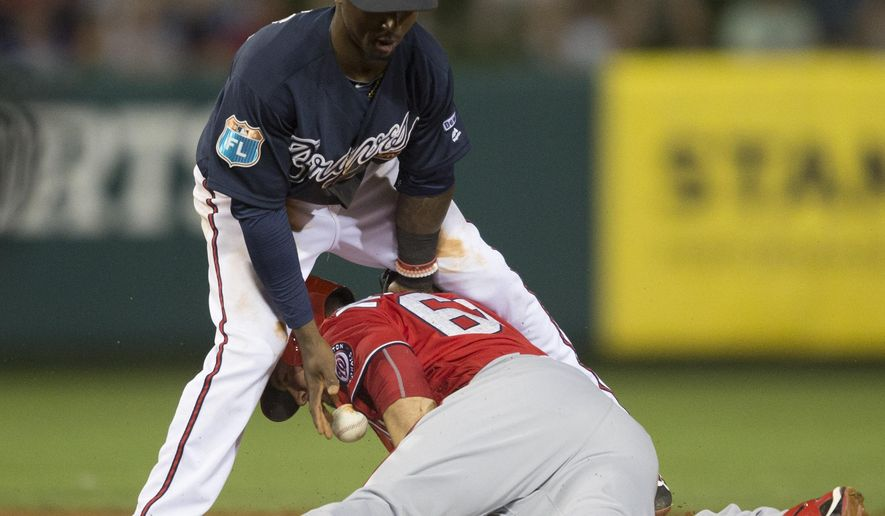 CORRECTS ALBIES' POSITION TO SECOND BASEMAN INSTEAD OF SHORT STOP - Atlanta Braves second baseman Ozzie Albies can not control the throw as Washington Nationals shortstop Jason Martinson (68) steals second base safely during a spring training baseball game, Saturday, March 12, 2016, in Kissimmee, Fla. (AP Photo/Willie J. Allen Jr.)