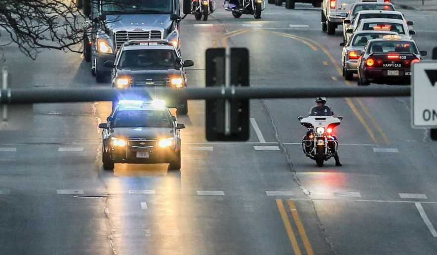 Police officers escort a flatbed truck transporting three elephants through downtown Omaha to the Henry Doorly Zoo on Friday, March 11, 2016. More than a dozen elephants were flown from Swaziland to the United States, being distributed to Dallas, Wichita, Kan., and Omaha. (AP Photo/Nati Harnik)
