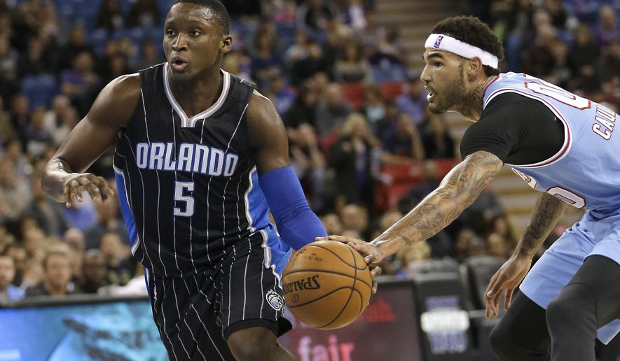 Orlando Magic guard Victor Oladipo, left, has the ball hit out of his hand by Sacramento Kings center Willie Cauley-Stein, right, during the first quarter of an NBA basketball game Friday, March 11, 2016, in Sacramento, Calif. (AP Photo/Rich Pedroncelli)
