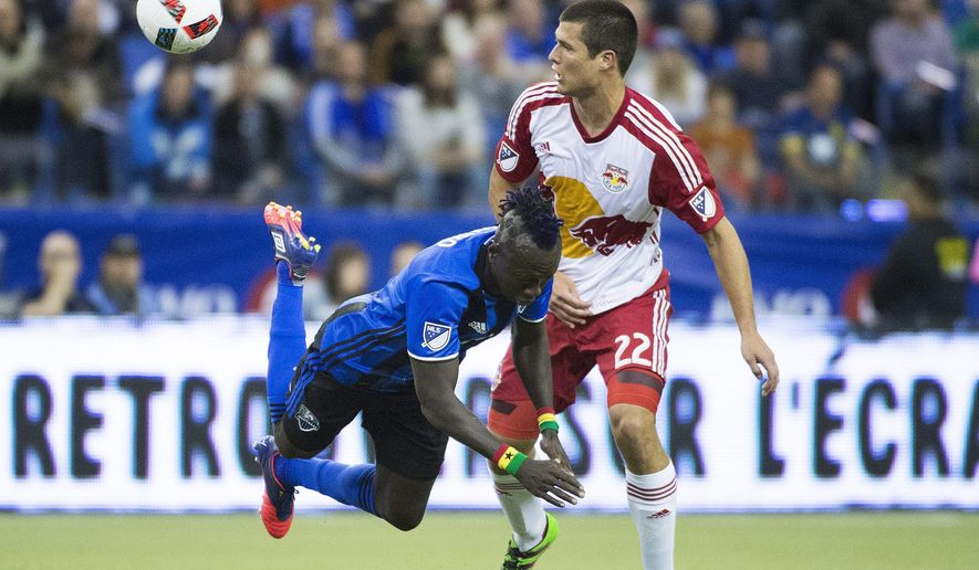 Montreal Impact's Dominic Oduro, left, is brought down by New York Red Bulls' Karl Ouimette during first half of their MLS soccer match in Montreal Saturday, March 12, 2016. (Graham Hughes /The Canadian Press via AP) MANDATORY CREDIT