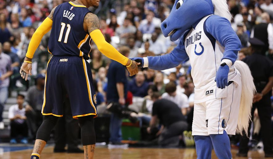 Indiana Pacers guard Monta Ellis (11) shakes hands with the Dallas Mavericks mascot before an NBA basketball game, Saturday, March 12, 2016, in Dallas. (AP Photo/Jim Cowsert)
