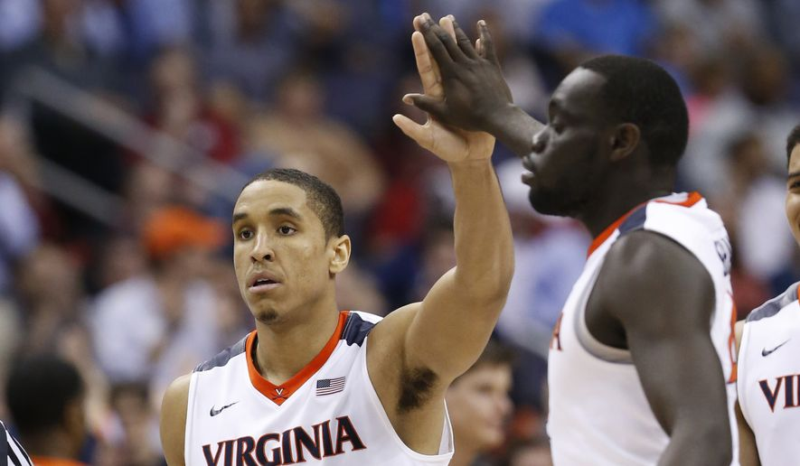 Virginia guard Malcolm Brogdon (15) gives a high-five to guard Marial Shayok (4) during the second half of an NCAA college basketball game against Miami in the Atlantic Coast Conference  men'stournament, Friday, March 11, 2016, in Washington. Virginia defeated Miami 73-68. (AP Photo/Steve Helber)