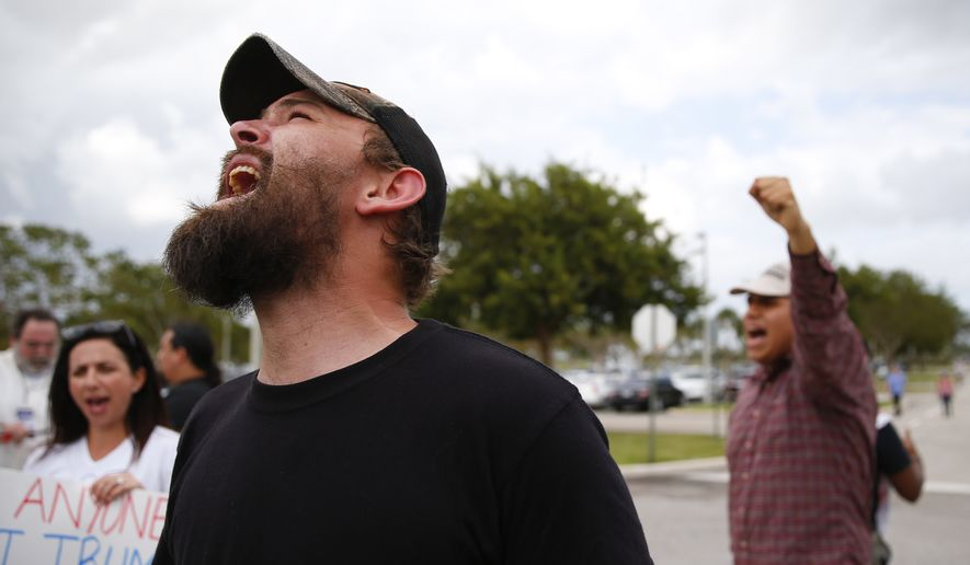 A protester yells outside a Republican presidential candidate Donald Trump campaign rally in Boca Raton, Fla., Sunday, March 13, 2016. (AP Photo/Paul Sancya)