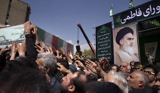 In front of a portrait of the late Iranian revolutionary founder Ayatollah Khomeini, mourners carry a flag draped coffin of an unknown Iranian soldier who was killed during the 1980-88 Iran-Iraq war, whose remains were recently recovered, during a ceremony commemorating the death anniversary of Fatima, the daughter of Islam's Prophet Muhammad, in Tehran, Iran, Sunday, March 13, 2016. (AP Photo/Vahid Salemi)