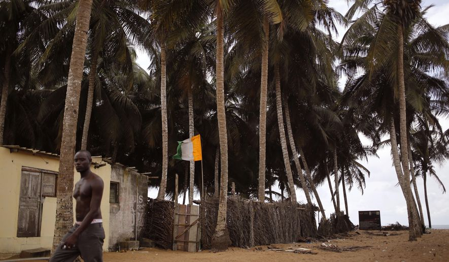 FILE-In this file photo taken on Tuesday, Oct. 27, 2015, a man, passes a home stead, with an Ivory Coast national flag, center, seen  at a fishing village renowned as a tourist hot spot visited by French and other tourist yearly in Grand Bassam, Ivory Coast. Assailants opened fire on beachgoers Sunday in Grand-Bassam, a historic resort town in Ivory Coast sending tourists fleeing through hotels. Photos posted to social media apparently taken at the scene showed bodies sprawled on the beach.  (AP Photo/Schalk van Zuydam, File)